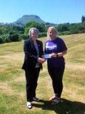 Lady President Rosie presents a cheque for £1095 to Caireen Mc Alister, rep for the Glens Floating Support of Inspire, a local charity which gives practical support to individuals and families coping with mental health issues. The money was generously donated by the Ladies and Gents of Cushendall Golf Club during Lady President's weekend in June.